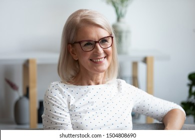 Head shot portrait close up smiling mature woman wearing glasses looking in distance, dreaming, thinking of future, older female with healthy smile sitting on couch at home, posing for photo
