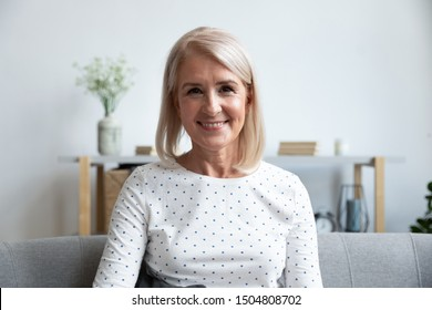 Head shot portrait close up smiling mature woman looking at camera, sitting on couch at home, beautiful older female grandmother making video call, teacher holding online lesson or recording vlog