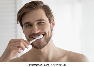 Head shot portrait close up smiling young man brushing teeth, looking at camera, personal oral hygiene concept, satisfied handsome guy enjoying morning routine, standing in bathroom