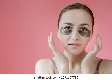Head shot portrait close up smiling young woman with under eye moisturizing patches mask looking at camera enjoying skincare procedure.