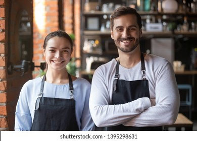 Head shot portrait of coffeehouse workers, employees wearing aprons, smiling waiter and waitress, looking at camera, baristas standing in cozy cafe with arms crossed, friendly restaurant staff