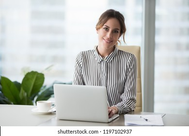 Head shot portrait of confident businesswoman at workplace, smiling woman employee sitting behind laptop and looking at camera. Staff at work.