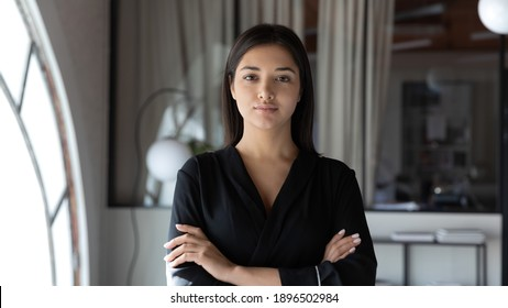 Head shot portrait confident Indian businesswoman hr manager standing in modern office with arms crossed, serious entrepreneur team leader mentor posing for corporate photo, looking at camera