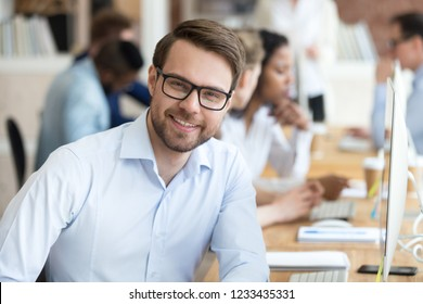 Head shot portrait confident smiling millennial businessman, happy satisfied trainee, intern at workplace, head of department having pleasure from work, look at camera