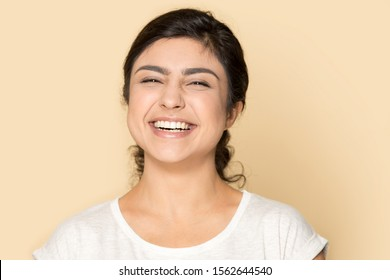 Head shot portrait excited beautiful Indian girl with healthy smile and perfect skin looking at camera, posing isolated in brown studio background, pretty female having fun, laughing at joke