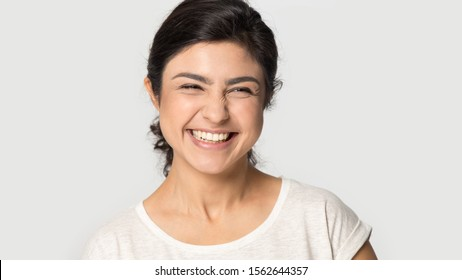 Head shot portrait excited Indian pretty girl laughing out loud at funny joke close up, happy beautiful young woman with beaming healthy smile standing isolated on grey studio background