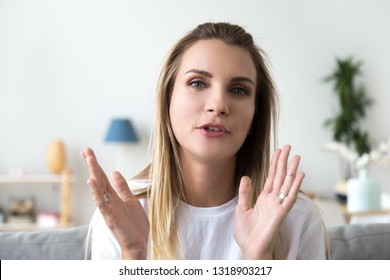 Head shot portrait friendly talking woman, looking at camera, making video call, attractive popular vlogger recording vlog or webinar for channel, explaining, sitting at home on cozy sofa