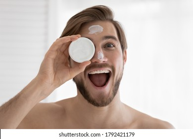 Head shot portrait funny overjoyed young man holding moisturizing face cream plastic jar, looking at camera, satisfied handsome male customer enjoying skincare beauty procedure after shaving