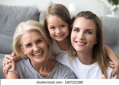 Head shot portrait granddaughter mother and grandmother sitting together on sofa at home looking at camera smiling feeling good and satisfied spend free time together. Happy mother day holiday concept