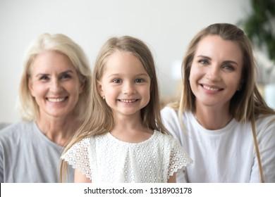 Head shot portrait grandmother, mother and daughter, three generations, looking at camera, smiling happy family posing at home, sitting on sofa, excited grandma with daughter and granddaughter