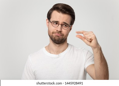 Head shot portrait guy isolated on grey background wearing glasses look at hand showing with fingers something small feels disappointed pity about little size insufficient length or thickness concept
