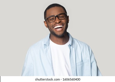 Head shot portrait handsome african good-looking man with snow-white healthy smile in casual blue shirt and glasses pose isolated on gray background, advertise eyewear store or dental services concept