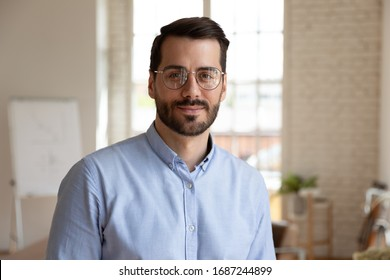 Head shot portrait of handsome bearded businessman wearing glasses looking at camera standing in office modern boardroom. Concept of successful entrepreneur, executive manager, head owner of company