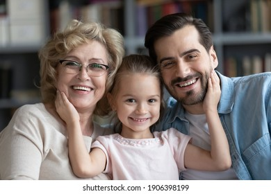 Head shot portrait of happy adorable little preschool 7s kid girl cuddling affectionate middle aged older granny and loving young father, posing for photo together at home, family relations concept.