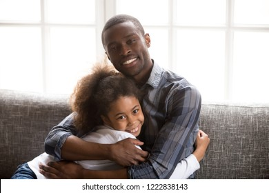 Head shot portrait happy African American family at home, loving father sincere embracing little preschooler daughter, sitting together on couch in living room, good relations in family look at camera