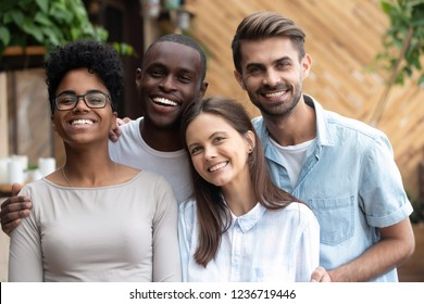 Head shot portrait of happy multiethnic friends look at camera, smiling diverse people having fun together in cafe, excited African Ameirican and caucasian colleagues, students posing, making photo