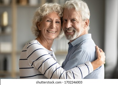 Head shot portrait happy older couple hugging, looking at camera, loving caring mature wife and husband with healthy toothy smiles posing for family photo at home, standing and embracing