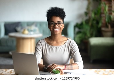 Head shot portrait of happy smiling African American woman sitting at table in cafe, looking at camera, excited female posing, working at computer, doing homework, preparing report in coffee house