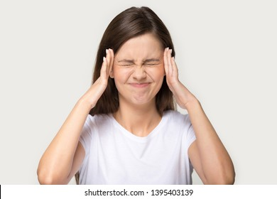 Head shot portrait isolated on grey background millennial frown woman closed eyes touch temples suffers from pounding throbbing tension headache, hate noise feels discomfort unwell unhealthy concept