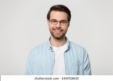 Head shot portrait isolated on grey studio background attractive smiling man wearing glasses blue shirt feels healthy positive posing indoors, representative of millennial gen, optic store ad concept