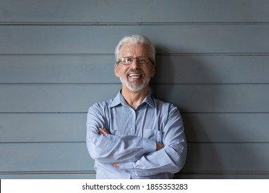 Head shot portrait laughing mature man wearing glasses standing with arms crossed on grey wooden wall background, overjoyed senior grandfather with healthy toothy smile looking at camera