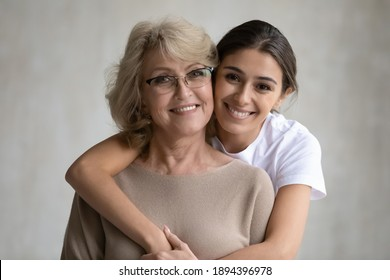 Head shot portrait loving grown up daughter hugging middle aged mother from back, looking at camera, happy mature grandmother and granddaughter posing for family photo on grey background together