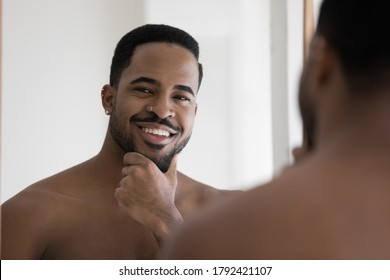 Head shot portrait mirror reflection smiling satisfied African American man touching beard, looking at camera, enjoying aftershave skincare procedure, applying lotion, standing in bathroom at home