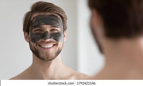 Head shot portrait mirror reflection smiling handsome man with black charcoal mask on face, pore removal, cleansing cosmetic product, skincare and treatment procedure, standing in bathroom