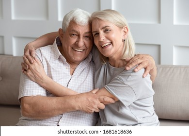Head shot portrait older wife and husband with healthy toothy smiles hugging, looking at camera, sitting on cozy sofa at home, happy adult middle-aged daughter embracing mature father, family photo