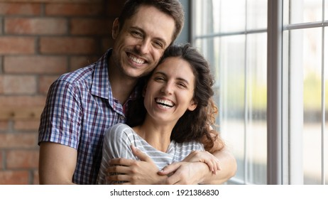 Head shot portrait overjoyed happy young couple hugging, standing at home, smiling husband embracing beautiful wife from back, looking at camera, enjoying tender moment, posing for family photo