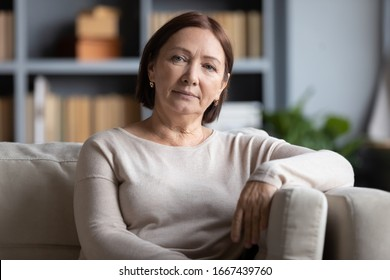 Head shot portrait peaceful tranquil middle aged old woman resting on cozy sofa alone at home. Pleasant happy senior mature 60s grandmother relaxing on couch in living room, posing for photo.