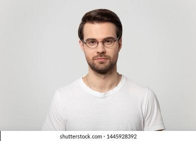 Head shot portrait of serious confident millennial man wearing glasses white t-shirt posing on grey studio background, guy advertise lens eyewear store sale, eyesight laser vision correction concept