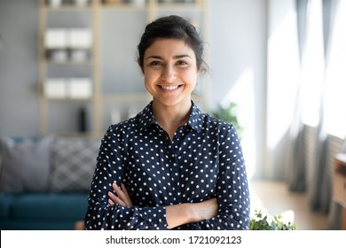 Head shot portrait smart confident smiling millennial indian woman standing with folded arms at home. Attractive young hindu teenager student girl freelancer looking at camera, posing for photo.