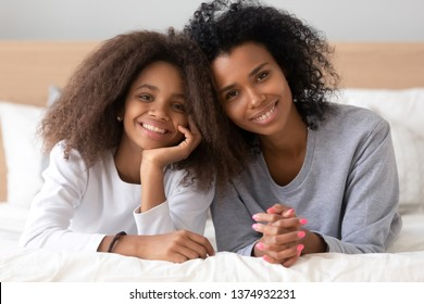 Head shot portrait of smiling African American mother and teen daughter lying on bed, looking at camera, posing for family photo in bedroom, black sisters or nanny and child spend time together
