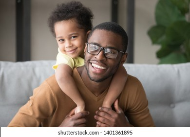 Head shot portrait of smiling African American father piggyback little son, attractive black man in glasses with toddler boy on back looking at camera, adorable child embracing dad, making video call