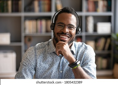 Head shot portrait smiling African American man wearing headphones and glasses looking at camera, posing for photo in modern cabinet, happy satisfied male customer service operator in headset