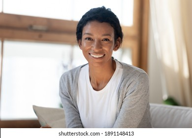 Head shot portrait of smiling beautiful young multiracial african american woman sitting on comfortable sofa. Sincere happy attractive millennial mixed race lady looking at camera, profile photo.