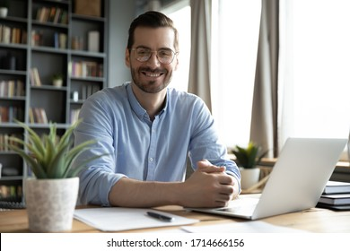 Head shot portrait smiling businessman wearing glasses sitting at work desk with laptop, looking at camera, confident satisfied man freelancer student posing for photo at workplace with computer