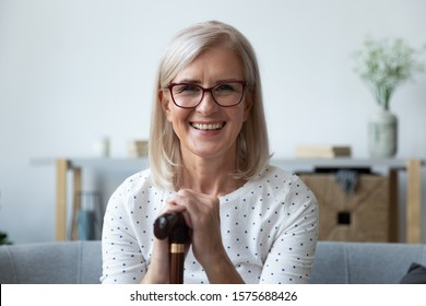 Head shot portrait smiling elderly woman sitting on couch at home posing looking at camera in hand holding walking stick wooden cane accessory, medical treatment, optimistic handicapped person concept