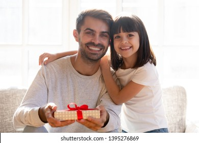 Head shot portrait of smiling father received gift from adorable daughter for birthday or fathers day, sitting on couch together, posing for photo, looking at camera, family celebration concept