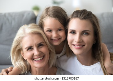 Head shot portrait of smiling grandmother, mother and daughter, looking at camera, excited granddaughter embracing mum and grandma, posing for family photo together at home, three generations
