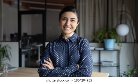 Head shot portrait smiling Indian businesswoman standing in modern office with arms crossed, confident successful young female employee intern looking at camera, posing for corporate photo