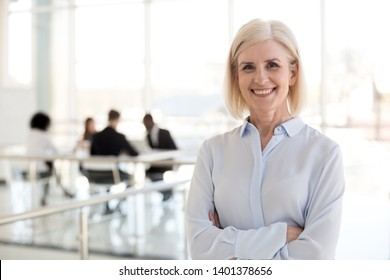Head shot portrait smiling mature businesswoman standing with arms crossed, posing for photo in company office hallway, middle-aged confident female employee making picture, looking at camera