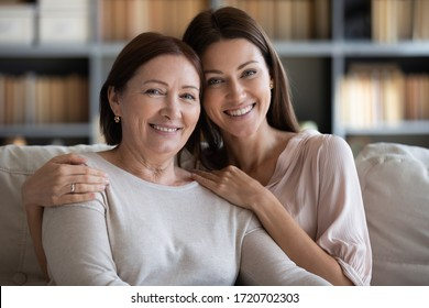 Head shot portrait smiling mature mother and daughter hugging, sitting on couch at home, looking at camera, young woman embracing older mum shoulders, family photo, two generations bonding