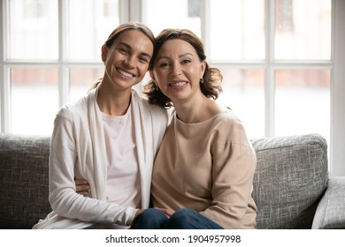 Head shot portrait smiling middle aged mother and grownup daughter hugging, sitting on cozy couch at home, happy young woman with mature mum posing for family photo together, looking at camera