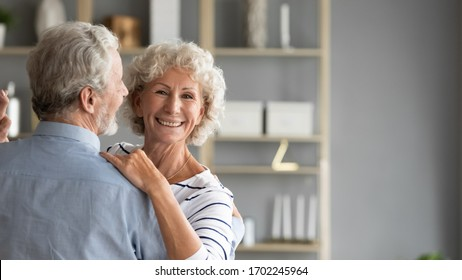 Head shot portrait smiling older woman dancing with man, happy mature wife and husband hugging, standing in living room, senior family enjoying tender moment, celebrating anniversary