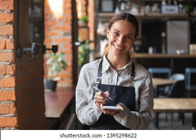 Head shot portrait of smiling waitress wearing black apron ready to take customer order, attractive woman with notebook and pen in hands looking at camera, standing in cozy coffeehouse, good service