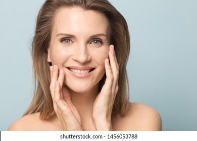 Head shot portrait smiling woman touching perfect smooth face skin, looking at camera, attractive young female with bare shoulders, natural beauty concept, close up isolated on studio background
