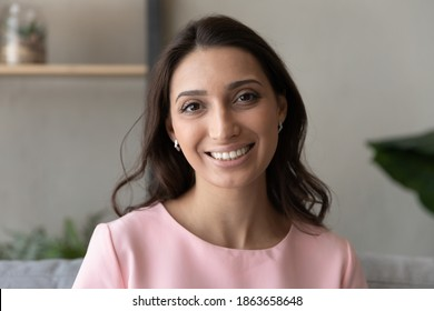 Head shot portrait social networks or dating application profile picture of attractive young happy indian arabic mixed race woman with toothy white teeth and perfect skin, looking at camera.