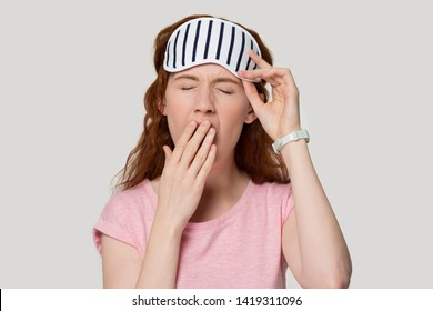Head shot portrait tired red-headed woman closed eyes cover mouth with hand yawning feels weak and sleepy on grey studio background, girl wearing sleeping eye mask goes to bed, late night time concept